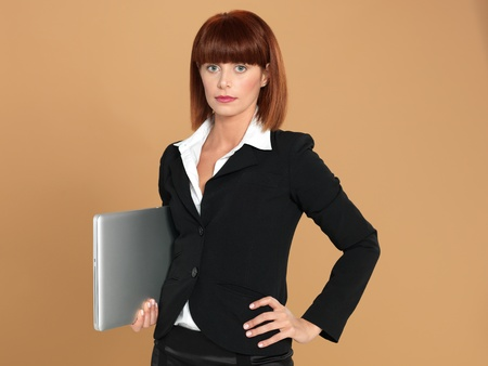 portrait of a beautiful, young businesswoman, holding a laptop, smiling, on beige background Stock Photo - 13239506