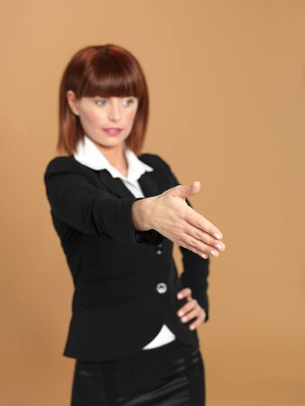 portrait of a beautiful, young businesswoman, with her arm forward, preparing for a hand shake, on beige background Stock Photo - 13238043