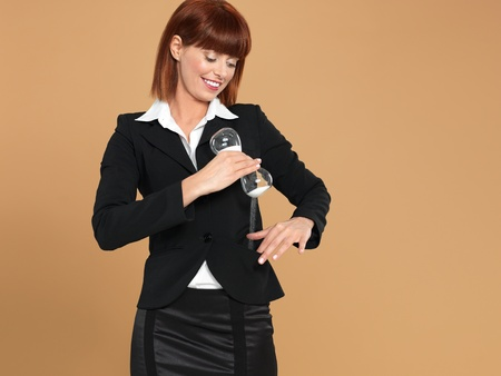 portrait of a beautiful, young businesswoman, pouring the sand of an hourglass in her pocket, on beige background Stock Photo - 13239511