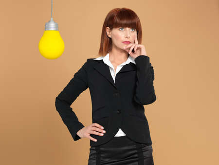 funny portrait of a beautiful, young businesswoman, with a light bulb, thinking, on beige background photo