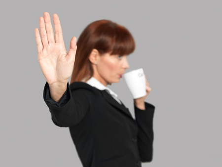funny portrait of a beautiful, young businesswoman, drinking her morning coffee, not wanting to be disturbed, on gray background photo
