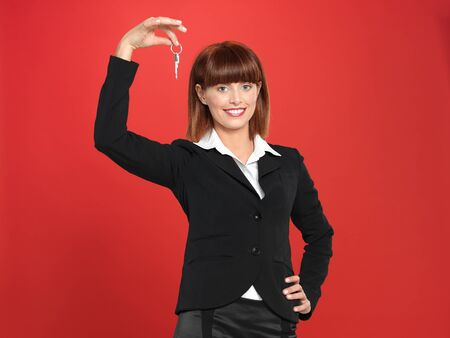 portrait of a beautiful, young realtor businesswoman, holding a house key in her hand, on red background photo