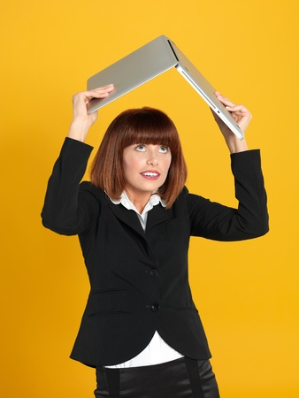 above head: portrait of a beautiful, young businesswoman, holding a laptop above her head as a shelter, on yellow background