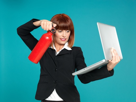 funny portrait of a beautiful, young businesswoman, using a fire extinguisher on her laptop, on blue background photo