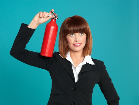 funny portrait of a beautiful, young businesswoman, using a fire extinguisher on her head, on blue background photo