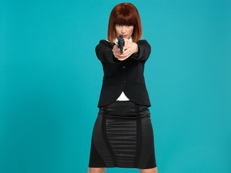 handguns: portrait of an agressive, beautiful, young businesswoman, pointing a gun in front of her, on blue background