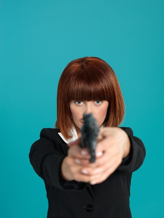women with guns: portrait of an agressive, beautiful, young businesswoman, pointing a gun in front of her, on blue background