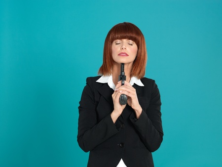holding gun to head: portrait of an agressive, beautiful, young businesswoman, pointing a gun to her chin, on blue background