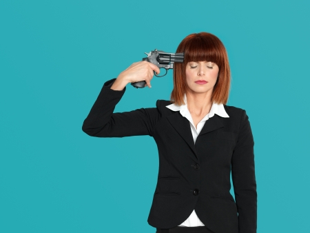 portrait of an agressive, beautiful, young businesswoman, pointing a gun  to her head, on blue background photo