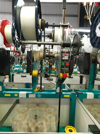 detail of an indoor industrial production line, in a thread factory photo