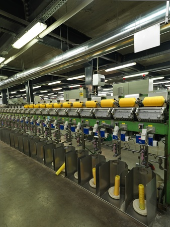 textile industry: detail of an indoor industrial production line, in a thread factory