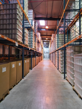 three shelves: interior perspective of a three storeys high hall, in an industrial warehouse, with products stored on shelves Stock Photo