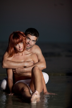 sexy, young couple playing kissing each other on the beach, after sunset, smilling Stock Photo - 13342751