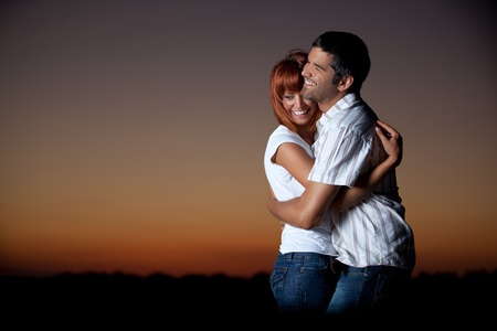 sexy, young couple playing holding each other on the beach, after sunset, smilling photo