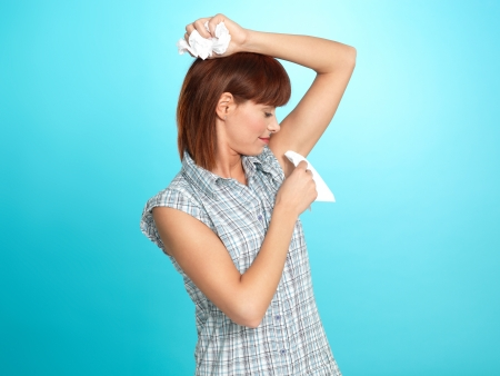 sweating: beautiful young woman, wiping her armpit sweat with napkins, on blue background