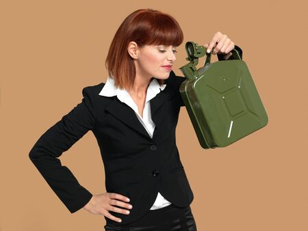 portrait of a young businesswoman, holding and smelling a gas canister, on beige background photo
