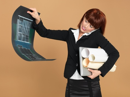 portrait of a bussy, young woman architect, holding a laptop and a blueprint, talking on the telephone, on beige background photo