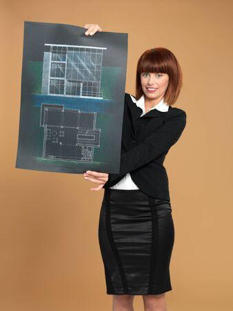 portret van een mooie, jonge vrouw architect, die een blauwdruk, op beige achtergrond