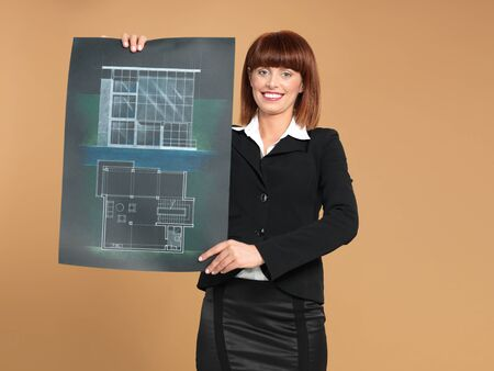 portrait of a beautiful, young woman architect, showing a blueprint, on beige background photo