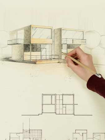 woman's hand drawing architectural perspective of modern house photo