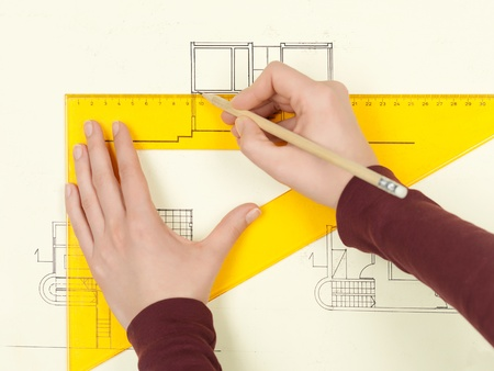 woman's hands drawing architectural blueprint of modern house photo