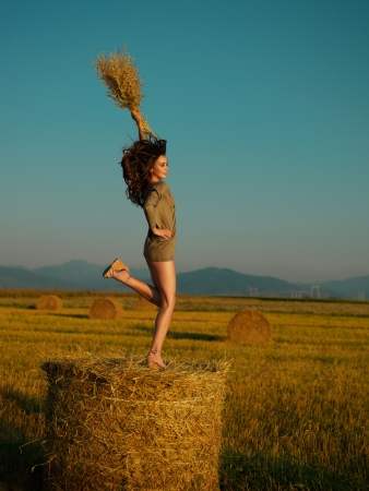 happy young woman jumping on one leg on a hay stack photo