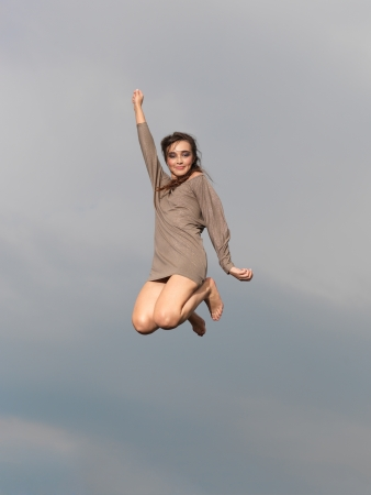 positive energy: happy young woman jumping for joy, smiling