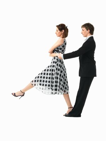 girl kick: passionate, young couple showing dance moves on white background Stock Photo