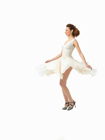 young girl feet: sexy young woman twirling around in a beautiful white dress, on white background Stock Photo