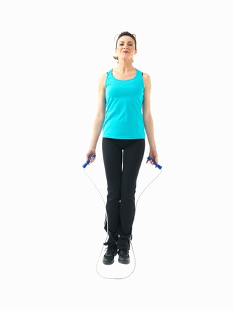 pretty young woman in fitness outfit jumping a skipping rope on white background photo
