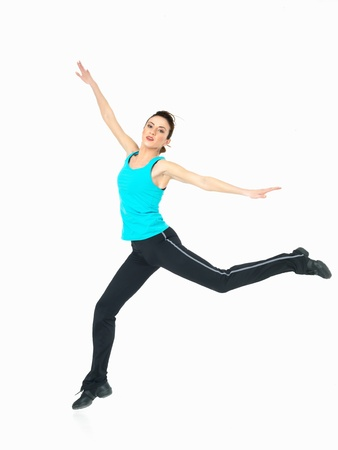 young woman in fitness outfit showing jumping moves on white background photo