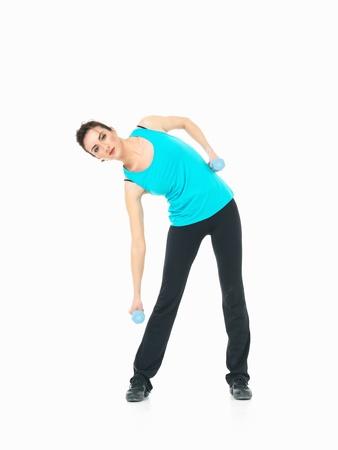 cintura perfecta: sexy mujer de fitness instructor, que muestra el ejercicio de pilates con los pesos pesados