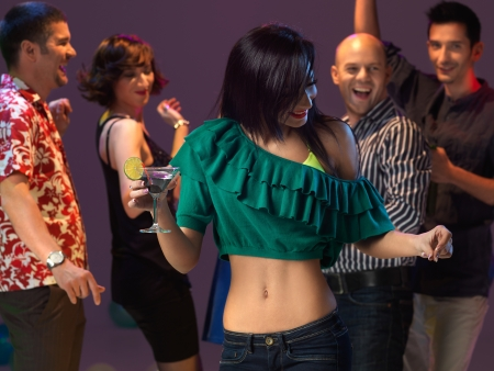 sexy, young woman dancing and drinking a cocktail on the dancefloor, in a night club photo