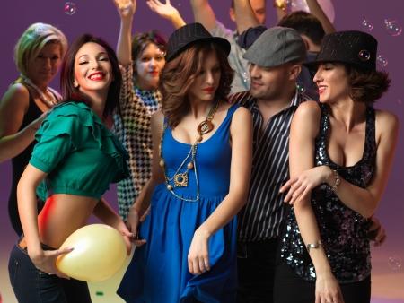 chicas bailando: las personas felices, j�venes flirteando y bailando en la pista de baile, en un club nocturno Foto de archivo