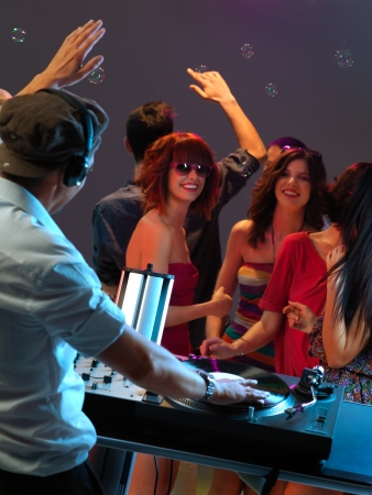 dj entertaining the happy, dancing crowd in a night club Stock Photo - 14807891