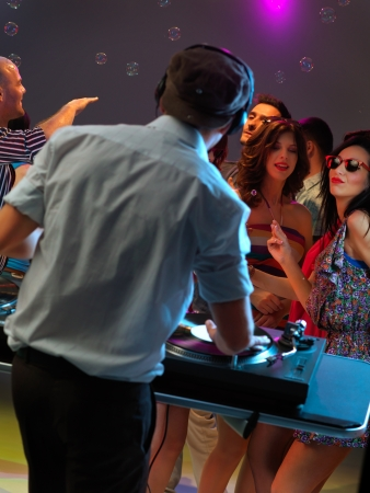 dj entertaining the happy, dancing crowd in a night club photo