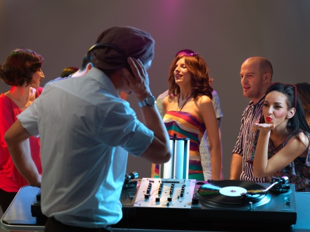 pretty young woman flirting with the dj in a night club photo