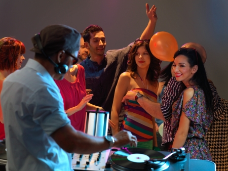 happy, young crowd dancing to the djs music in a night club photo