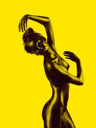 artistic nude: artistic nude of a young woman with black painted skin and yellow background, in a dance movement Stock Photo