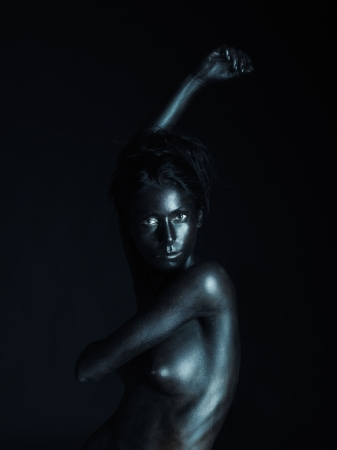 nude art model: artistic low-key nude portrait of young woman, painted in black, on black background, looking into the camera