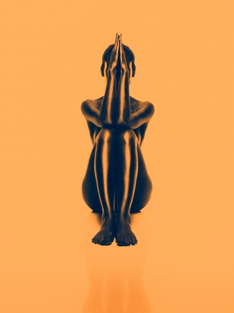 artistic nude: artistic nude of a young woman sitting down in a symmetrical position, on orange background Stock Photo