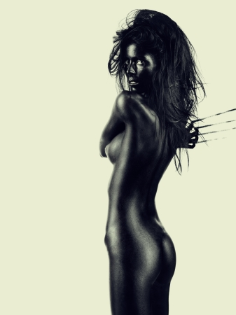 naked black woman: artistic nude of a beautiful, young woman, with her back at the camera, looking over her shoulder, leaving scratch marks on the wall behind her