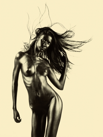 naked silhouette: artistic nude of a young woman with black painted skin on beige background, in a dance movement, with her hand in her hair