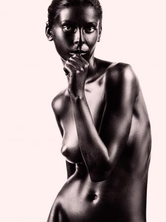 desnudo artistico: retrato desnudo art�stico de una mujer joven, pintado en negro, sobre fondo beige, con el dedo en la boca Foto de archivo