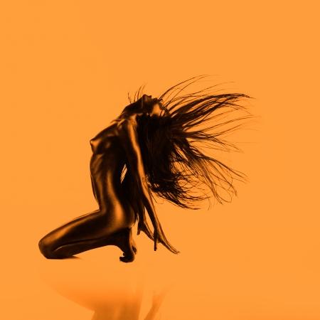 desnudo artistico: desnudo artístico de una mujer joven con la piel pintada de negro sobre fondo naranja, sentado en sus rodillas, tirando el pelo hacia atrás Foto de archivo