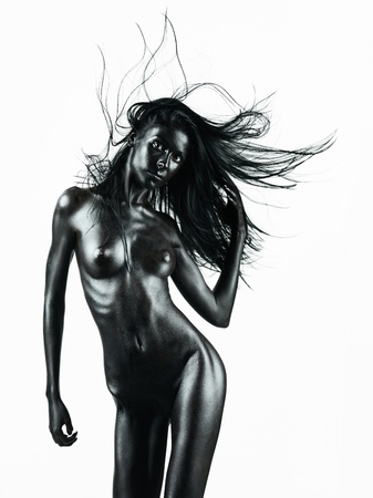 nude art model: artistic nude of a young woman with black painted skin isolated on white  background, in a dance movement, with her hand in her hair