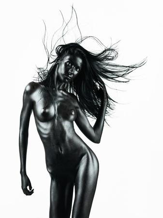 desnudo artistico: desnudo artístico de una mujer joven con la piel pintada de negro sobre fondo blanco, en un movimiento de la danza, con la mano en el pelo