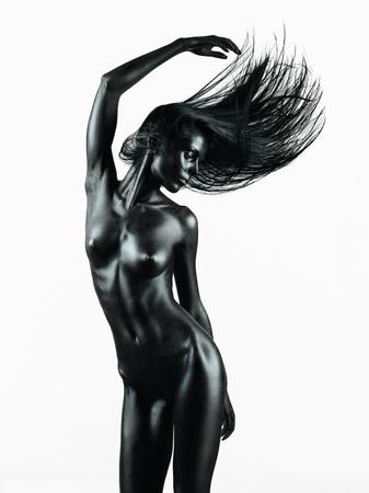 desnudo artistico: desnudo artístico de una mujer joven con la piel pintada de negro sobre fondo blanco, en un movimiento de baile con su mano en el aire