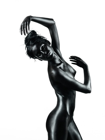 artistic nude: artistic nude of a young woman with black painted skin,isolated on white background, in a dance movement Stock Photo