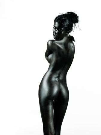 desnudo artistico: desnudo artístico de una mujer joven con la piel pintada de negro, aislados en fondo blanco, de pie, de espaldas a la cámara, mirando sobre su hombro